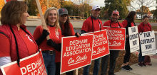 Dedham educators in red, on a picket line, with red and white signs.